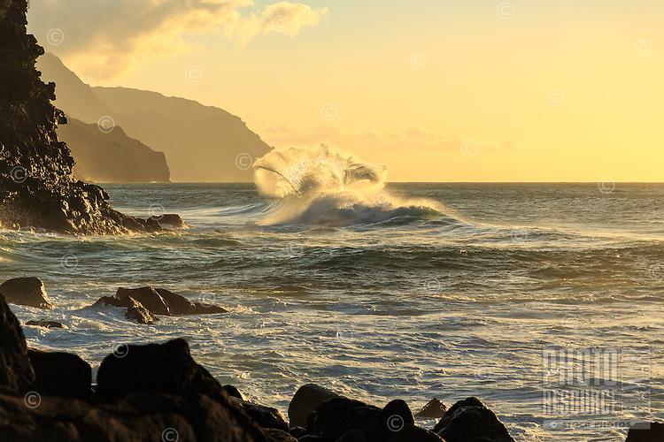 A wave shaped like the tail of a whale is backlit by the setting sun, Ke'e Beach, Na Pali Coast, Kaua'i.