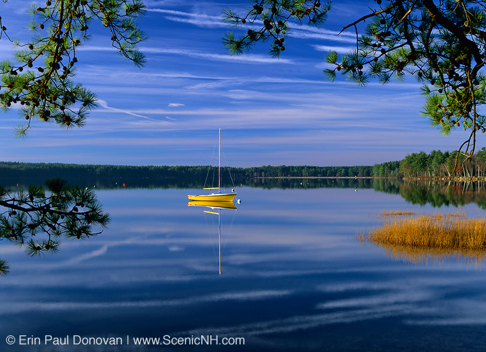 Reflection of yellow sailboat in Lake Massabesic in Auburn, New Hampshire at sunrise. Located in Manchester and Auburn, this lake covers over 2,500 acres, and it is the drinking water supply for the Manchester area.