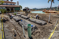 Water capture; workmen installing cisterns in water conserving Southern California garden; design Urban Water Group