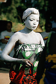 Ujiji, Tanzania. Traditional dancer with whitened body wearing green and red printed cotton wrap cloths.