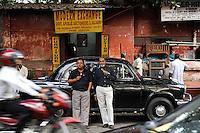 INDIA Westbengal Calcutta Kolkata, people eat ice cream in front of black HM Ambassador car/ INDIEN Westbengalen Megacity Kalkutta, Menschen essen Eis vor HM Ambassador Auto in der Russell Street