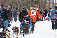 Aaron Peck and team run past spectators on the bike/ski trail near University Lake with an Iditarider in the basket and a handler during the Anchorage, Alaska ceremonial start on Saturday, March 7 during the 2020 Iditarod race. Photo © 2020 by Ed Bennett/Bennett Images LLC