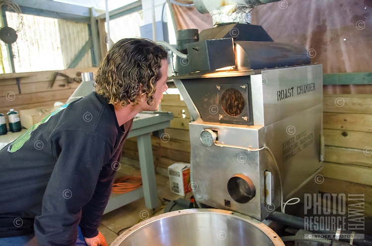 Business owner Kaleo checking on roasting process, Kaleo's Koffee, Hamakua area, Big Island.