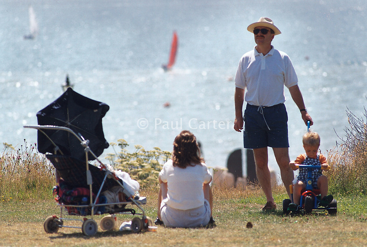 Mother and father with their small children enjoying a day by the sea.