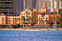 "The Royal Hawaiian Hotel or """"pink palace"""", shot from the ocean with hundreds of tourists on the beach and a blue and white striped catamaran on the beach."