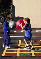 Recess at Carl Munck Elementary School. Playground activities. Playing ball. Oakland, California.
