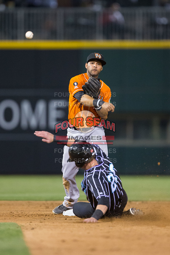 Norfolk Tides second baseman Robert Andino (3) makes a throw to first base as Danny Hayes (20) of the Charlotte Knights slides into second base at BB&T BallPark on May 2, 2017 in Charlotte, North Carolina.  The Knights defeated the Tides 8-3.  (Brian Westerholt/Four Seam Images)