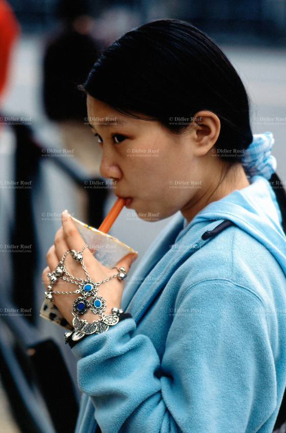 China. Shanghai. Downtown. City center. Young woman dressed in sports outfitt drinks a soft drink in the streets. Her left hand is covered by various jewelleries.  © 2002 Didier Ruef
