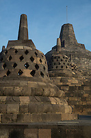 Borobudur, Java, Indonesia.  Three Small Stupas, Topmost Stupa in Background.  The third one, with square-shaped openings, symbolizes the overcoming of passions as one approaches Nirvana.