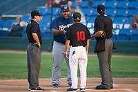 Helena Brewers manager Nestor Corredor (9) meets with Great Falls Voyagers manager Tim Esmay (10) and umpires Philip Bando (left) and Edgar Huerta-Morales (right) prior to their Pioneer League game at Centene Stadium on August 18, 2017 in Helena, Montana.  The Voyagers defeated the Brewers 10-7.  (Brian Westerholt/Four Seam Images)