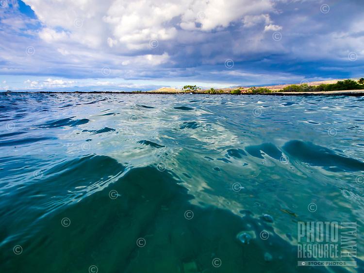 Water shimmers under a cloudy sky at Mahai'ula Beach (part of Kekaha Kai State Park), Kona Coast, Big Island.