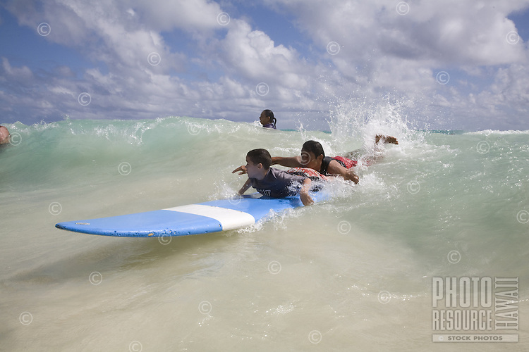 Kids learning how to surf in a charity surfing event