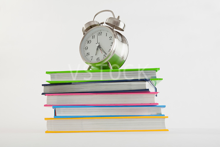 Stack of colorful books with alarm clock on top