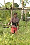 A Garifuna workman with dreadlocks clears a field with a machet in Barranco village in southern Belize.  Village.