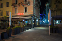 """Switzerland. Canton Ticino. Lugano. Vanini is a famous restaurant cafe place on Piazza Riforma. Saturday Night Life. Nobody in the streets. All restaurants are closed due the the Coronavirus (also called Covid-19). Due to the spread of the coronavirus, the Federal Council has categorised the situation in the country as """"extraordinary"""". It has issued a recommendation to all citizens to stay at home, especially the sick and the elderly. The Federal Council (German: Bundesrat, French: Conseil fédéral, Italian: Consiglio federale, Romansh: Cussegl federal) is the seven-member executive council that constitutes the federal government of the Swiss Confederation. From March 16 the government ramped up its response to the widening pandemic, ordering the closure of bars, restaurants, sports facilities and cultural spaces. Only businesses providing essential goods to the population – such as grocery stores, bakeries and pharmacies – are to remain open. 21.03.2020 © 2020 Didier Ruef"""