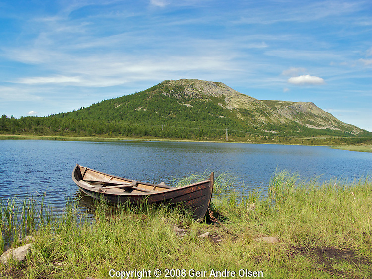 An old wooden boat on a lake in the Norwegian mountains close to Ringebu.