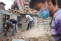 Nepalese men remove rubble from his destroyed house in Shanku near Kathmandu, Nepal. May 9, 2015