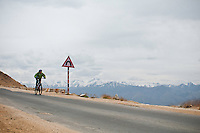 Mountain biker speeding down the highest motorable road in the world,  Himalayan Mountains, Ladakh, India.
