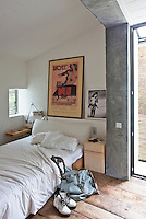 This simple bedroom is decorated with a framed retro poster and a black and white photograph