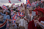 Ascot Horse Racing Berkshire Uk. Racegoers wave the Union Jack flag while singing Land of Hope and Glory around the band stand at the end of the days racing.