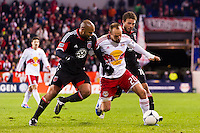 Joel Lindpere (20) of the New York Red Bulls is defended by Robbie Russell (3) and Nick DeLeon (18) of D. C. United during the second leg of the MLS Eastern Conference Semifinals at Red Bull Arena in Harrison, NJ, on November 8, 2012.
