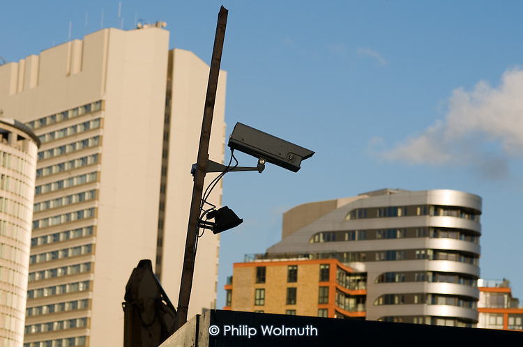 A surveillance camera overlooks construction work on Merchant Square at Paddington Basin, in front of the completed West End Quay development and the Hilton  London Metropole hotel.