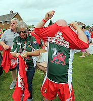 Pictured: Participants prepare by wearing red t-shirts in Cardiff, Wales, UK. Wednesday 24 August 2016<br /> Re: The largest rugby scrum has been achieved by Golden Oldies at University Fields in Cardiff south Wales, UK. It was refereed by welsh international referee Nigel Owens. Guinness World Records has verified the new record in which 1297 people took part in.