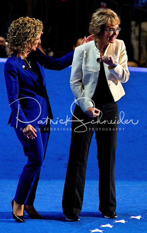 Rep. Debbie Wasserman Schultz, D-Fla., left, escorts former Rep. Gabrielle Giffords, D-Ariz., to the stage to lead the pledge of allegiance at the Democratic National Convention at Time Warner Cable Arena in Charlotte, N.C.