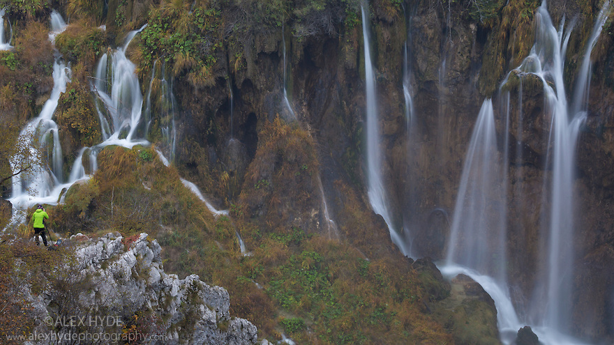 A series of waterfalls known as 'Sastavci' that cascade between mountain lakes, with photographer in foreground for scale. Plitvice Lakes National Park, Croatia. November.