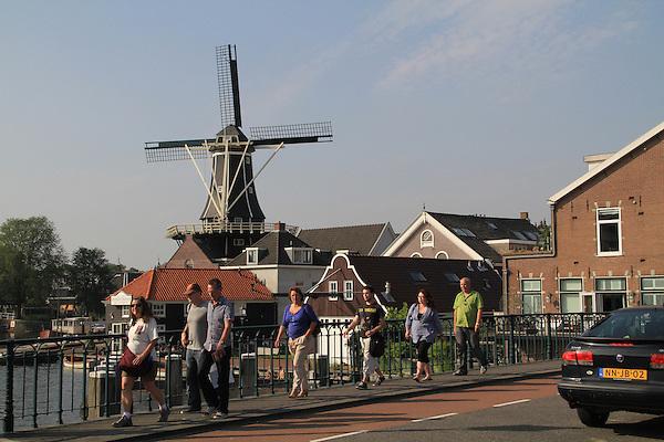 People crossing bridge over the Spaarne River, with the De Adriaan Windmill Museum Haarlem, Holland, Netherlands.