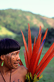 Brazil. Yanomami Indian Shaman with traditional decorative red Macaw feather amulets and face paint design.
