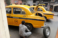 INDIA West Bengal, Kolkata, HM Ambassador yellow cab, change of flat tyre, the car is still produced new at Hindmotor factory after license of Oxford Morris / INDIEN Westbengalen Kalkutta, Ambassador Taxi, Wechsel eines platten Reifens, der HM Ambassador laeuft heute noch neu nach Vorlage des Oxford Morris bei HM Hindustan Motors vom Band