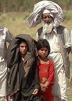 Refugees from Swat district wait for food to be distributed at the Swabi Refugee camp. The camp is run by Red Cross/Red Crescent (ICRC), and currently houses around 18,000 refugees. The Pakistani government began an offensive against the Taliban in the Swat Valley in April 2009, which led to a major humanitarian crisis. Up to two million civilians were estimated to have been displaced by the fighting.