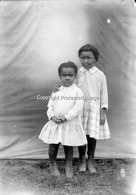 MATCHING. The matching shoes, dresses, and chain necklaces with small medals all suggest that these girls are sisters.<br /> <br /> Photographs taken on black and white glass negatives by African American photographer(s) John Johnson and Earl McWilliams from 1910 to 1925 in Lincoln, Nebraska. Douglas Keister has 280 5x7 glass negatives taken by these photographers. Larger scans available on request.