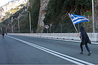 Pictured: A young migrant walks on the motorway with a greek flag Thursday 25 February 2016<br /> Re: Hundreds of migrants, including families with young children, that were stranded at Tempe in central Greece, were forced to walk on foot on the motorway to reach Idomen, about 168 kilometres away, in the northern part of the country, at the Greek FYRO Macedonian border. Local police were at first escorting them, then made sure that they were safely transported on coaches.