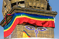 Nepal, Kathmandu, Swayambhunath.  The All-Seeing Eyes of the Buddha Gaze out from above the Stupa of Swayambhunath.  Below the eyes is the Nepali number one, symbolizing the unity of life.   The main stupa survived the earthquake of April 2015, but the remainder of the complex was severely damaged.