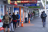 The queue for Karori Mall supermarkets. Karori town centre at 4pm, Wednesday, during lockdown for the COVID19 pandemic in Wellington, New Zealand on Wednesday, 22 April 2020. Photo: Dave Lintott / lintottphoto.co.nz