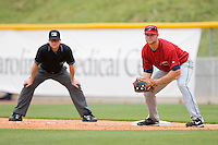 First baseman Wes Hodges #11 of the Columbus Clippers looks for a possible pick-off throw as firs base umpire Jon Berry looks on during a game against the Charlotte Knights at Knights Stadium May 25, 2010, in Fort Mill, South Carolina.  Photo by Brian Westerholt / Four Seam Images