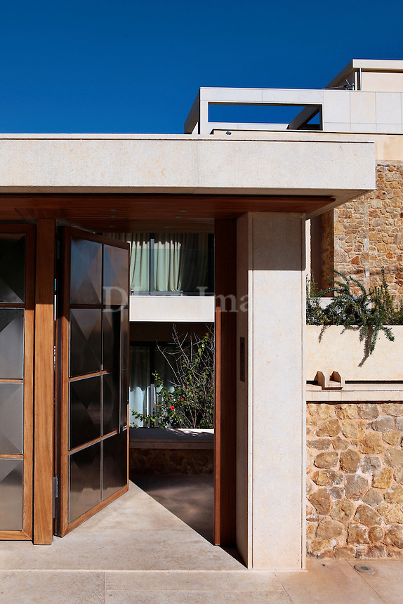 On a quiet hill in Porto Rafti, a coastal area of Athens, is a house that serves perfectly the needs of the Gougousi's family. The entrance of the three level house is from the side of the mountain with a view to the sea.
