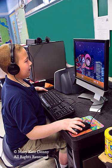 Autistic male second grade child in uniform wears headphones and sits at desk using mouse on a LCD computer away from other children in public school classroom in New Orleans, Louisiana