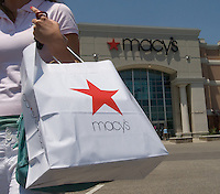 Shopper walks from Macy's store in a mall after purchase.
