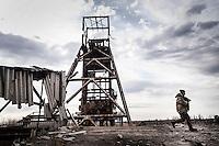 """UKRAINE, 03.2015, Peski. Bei dem umkaempften Dorf unweit des Donezker Flughafens steht der inzwischen zerschossene Bergwerks-Foerderturm """"Neba"""" (Himmel), der dem """"Rechter Sektor"""" Freiwilligenbataillon als MG-Nest diente.   Near the frontline village close to the Donetsk airport the coal shaft tower """"Neba"""" (Sky) has been destroyed which used to serve as machine gun position for the """"Right Sector"""" volunteer battalion.  © Arturas Morozovas/EST&OST"""
