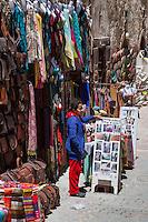 Essaouira, Morocco.  Souvenir Vendor Standing by a Sign offering Henna Tattoos, Rue de la Skala.