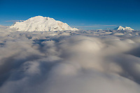 Mt Denali and Mount Foraker rise about a cloud layer at about 10,000 feet. Denali National park, Alaska