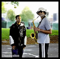 Teen admiring older musician playing the sax, sharing a love of the same instrument. JAZZ.