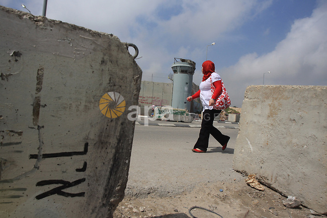Palestinian woman walks near Qalandia checkpoint between the West Bank city of Ramallah and Jerusalem, Monday, March 29, 2010. Israel imposed a closure on the West Bank as a security measure for the duration of the weeklong Passover holiday. The routine measure bars almost all Palestinians from entering Israel. Photo by Issam Rimawi