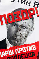 "Moscow, Russia, 13/01/2013..A mud-spattered portrait of President Vladimir Putin with the word ""Shame written across it at an opposition protest. Thousands of opposition protesters carried posters of President Vladimir Putin and members of the Russian parliament with the word ?Shame? written in red at a protest called the March Against The Scoundrels. The protest was against the new law banning the adoption of Russian children by Americans, widely seen as a response to the recently passed USA Magnitsky Act."