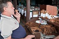 Cuba, Pinar del Rio Region, Viñales (Vinales) Area.  A torcedor (cigar roller) pauses in his work.