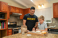 Happy caucasian Army dad off duty at home with family. Model released, DOD compliant for commercial or promotional use, stock photograph.