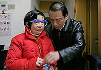 11 year old Liu Fangyuan(Yuan Yuan) drinks from a tube of a pair of funny glasses while her father Liu Yuanlin stands by her at their apartment in Nanjing, China. In 2002, Yuan Yuan's aunt poured sulfuric acid on her face after losing a housing dispute with Yuan Yuan's father in regards to a 40 squared meter apartment. The attack blinded and seriously disfigured Yuan Yuan, while her aunt is serving a life sentence in prison, Yuan Yuan and her family awaits a controversial face transplant...PHOTO BY SHEN / SINOPIX